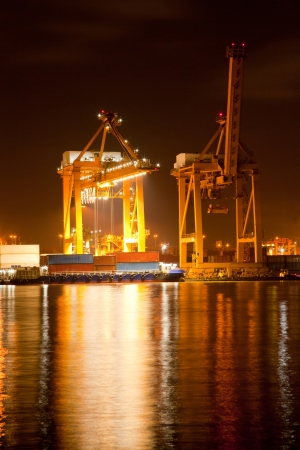Container stacks and crane bridge in shipyard at Night for cargo and Logistic background photo