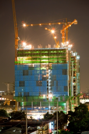 elevation: Big Construction Site with Working Cranes at dusk for Business Background Stock Photo