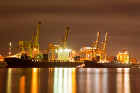 Container stacks and crane in shipyard at dusk for cargo Goods and Logistic background photo