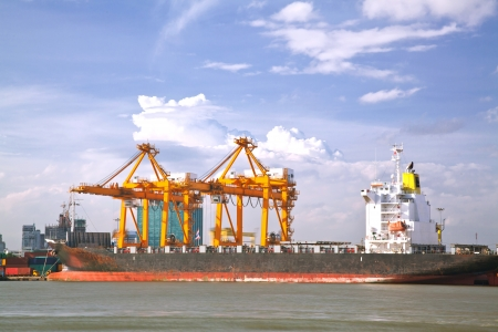 industrail: Container Cargo freight Industrail ship with working crane bridge unloading and loading goods in Bangkok shipyard Terminal for Logistic Import Export background Stock Photo