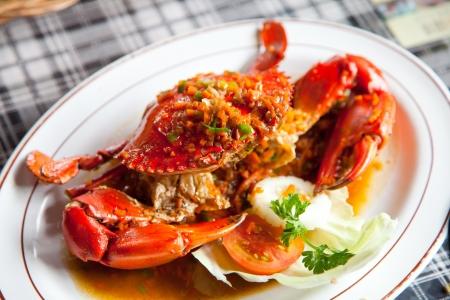 cangrejo: cangrejos cocidos con salsa picante en un plato blanco (atención selectiva)