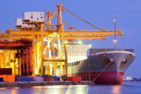 送料: 工業のコンテナー貨物の貨物船ロジスティック インポートエクスポートの背景の夕暮れ時にクレーン橋造船所での作業に