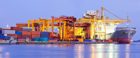 Panorama of Industrial Container Cargo freight ship with working crane bridge in shipyard at dusk for Logistic Import Export background