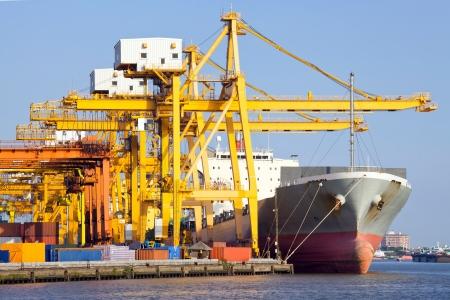Cargo industrial ship unloading goods at Terminal Port