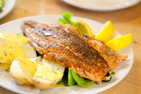 グルメとサーモンのステーキをグリル焼きポテトとレモンの食事 写真素材