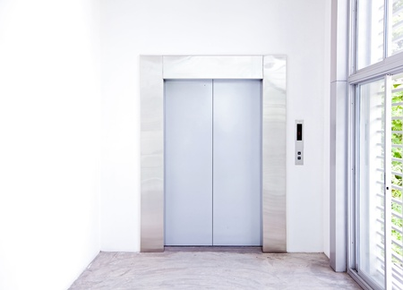 Front view of a modern elevator with closed doors in lobby photo