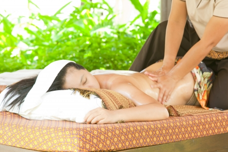 Back oil Massage Spa with Hand in tropical garden for wellness and healthy background photo