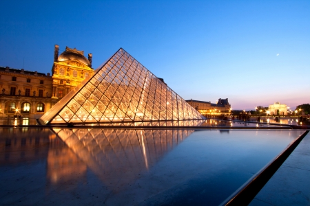 museum: PARIS-APRIL 16: Reflection of Louvre pyramid shines at dusk during the Summer Exhibition April 16, 2010 in Paris. Louvre is the biggest Museum in Paris displayed over 60,000 square meters of exhibition space.