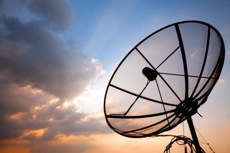 Gran plato de telecomunicaciones por satélite a través de la puesta del sol cielo Foto de archivo