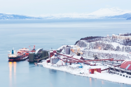mining town: Industrial Container Cargo freight ship with working crane bridge in shipyard at Iron Ore Mine Factory Plant in Narvik Norway