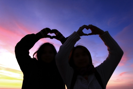 thier: Silhouette of two grils forming thier hand to heart shape Stock Photo