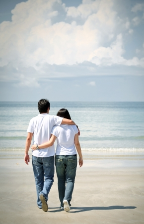romantic couples walking together on the beach photo