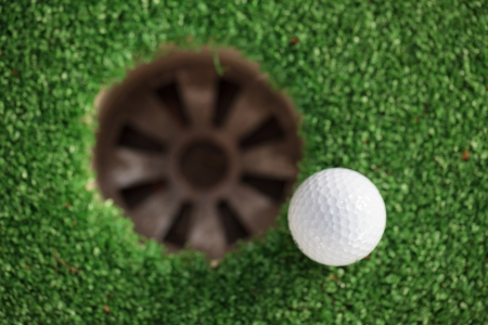 golf ball on lip of cup (Selective focus at golf ball) photo