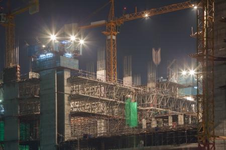 cantieri edili: cantiere con gru in movimento al crepuscolo Editoriali