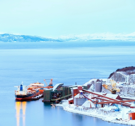 mining ship: Panorama Industrial Container Cargo freight ship with working crane bridge in shipyard at Iron Ore Mine Factory Plant in Narvik Norway Stock Photo