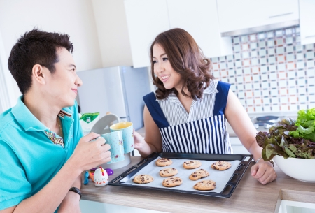 Young happy couples in domestic kitchen with breakfast (Selective focus at man)