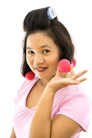 poised: pretty young adult woman with hair curlers on white background