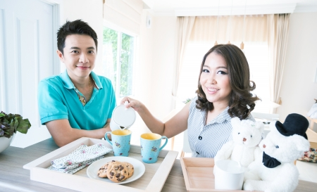 Young happy couples in domestic kitchen with breakfast photo