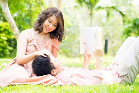 to lap: Couple relaxing in the garden, young man reading a book and lying on his girlfriend lap
