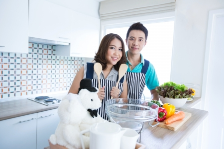 family kitchen: Young happy couples prepare vegetable salad in domestic kitchen Stock Photo