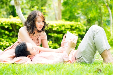 Couple relaxing in the garden, young man reading a book and resting on his girlfriend lap photo