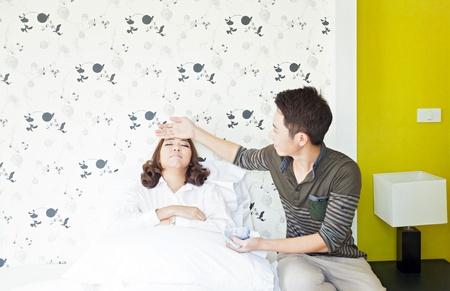 persona sentada: Adultos j?venes de marido takecare su esposa enferma en el dormitorio (atenci?n selectiva a la mujer)