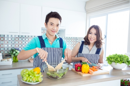 Young happy couples in domestic kitchen photo