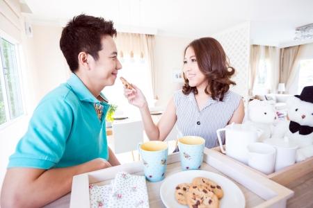 Jeunes couples heureux dans la cuisine familiale avec petit-déjeuner