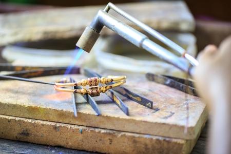 Goldsmith travailler avec un bracelet traditionnel thai Banque d'images