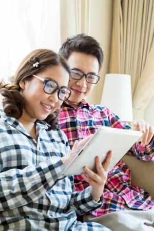 Couples with a tablet computer in living room photo