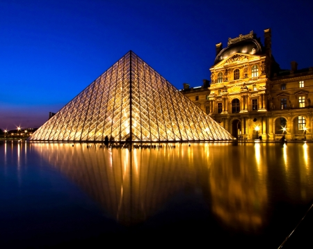 PARIS-APRIL 16: Reflection of Louvre pyramid shines at dusk during the Summer Exhibition April 16, 2010 in Paris. Louvre is the biggest Museum in Paris displayed over 60,000 square meters of exhibition space. Stock Photo - 19777777