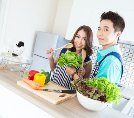 Jeunes couples heureux dans la cuisine domestique Banque d'images
