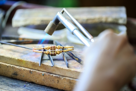 Goldsmith working with a thai traditional bracelet photo