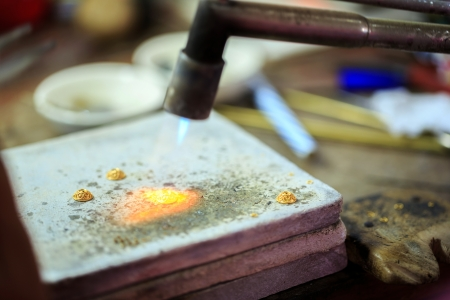 making a fire: Goldsmith working with a thai traditional gold