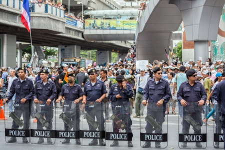 loyalist: BANGKOK,THAILAND- JUNE 30 : Unidentified polices stand guard on pathumwan road during a Guy Fawkes anti-government rally on Jun 30, 2013 in Bangkok, Thailand.