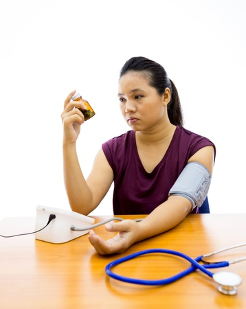 Young adult woman unhappy with her self blood pressure test (Selective focus at woman) photo