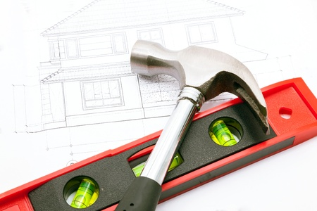 budget repair: hammer and water level over a construction drawing of a house blueprint