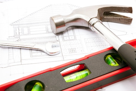 Construction tools over a construction drawing of a house blueprint