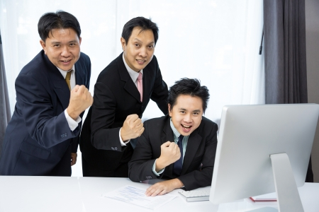 discuss: Team of businessmen analysis their business with computer desktop Stock Photo