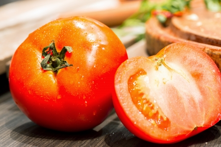 Tomatoes, cooked with herbs for the preservation on the old wooden table. Stock Photo