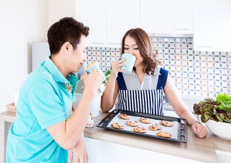 Young happy couple in domestic kitchen with breakfast photo