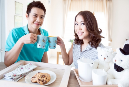 Young happy couple in domestic kitchen with breakfast