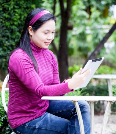 Smiling young woman using tablet PC for working in garden photo
