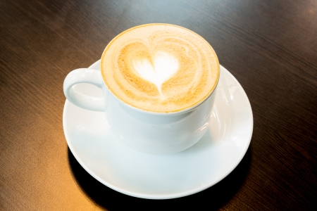 Cup of latte coffee with heart symbol photo