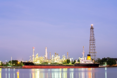 mining ship: landscape of Oil refinery plant along river with tanker at dusk