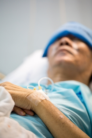 mature senior man Patient sleeping in hospital bed (Selective focus at hand) photo