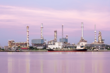 mining ships: landscape of Oil refinery plant along river with tanker at dusk