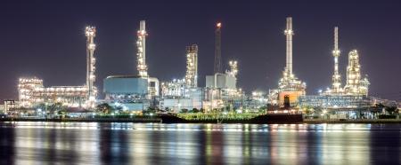 Panorama del paisaje de la planta de refinería de petróleo a lo largo del río con cisterna en la noche