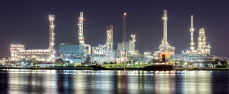 industria quimica: Panorama del paisaje de la planta de refinería de petróleo a lo largo del río con cisterna en la noche