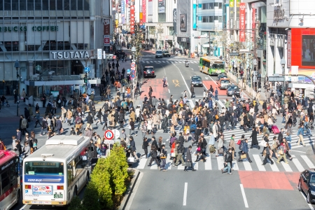 implementations: TOKYO - DECEMBER 11:Pedestrians cross at Shibuya Crossing December 11, 2013 in Tokyo, Japan. The crosswalk is one of the worlds most famous implementations of a scramble crosswalk.